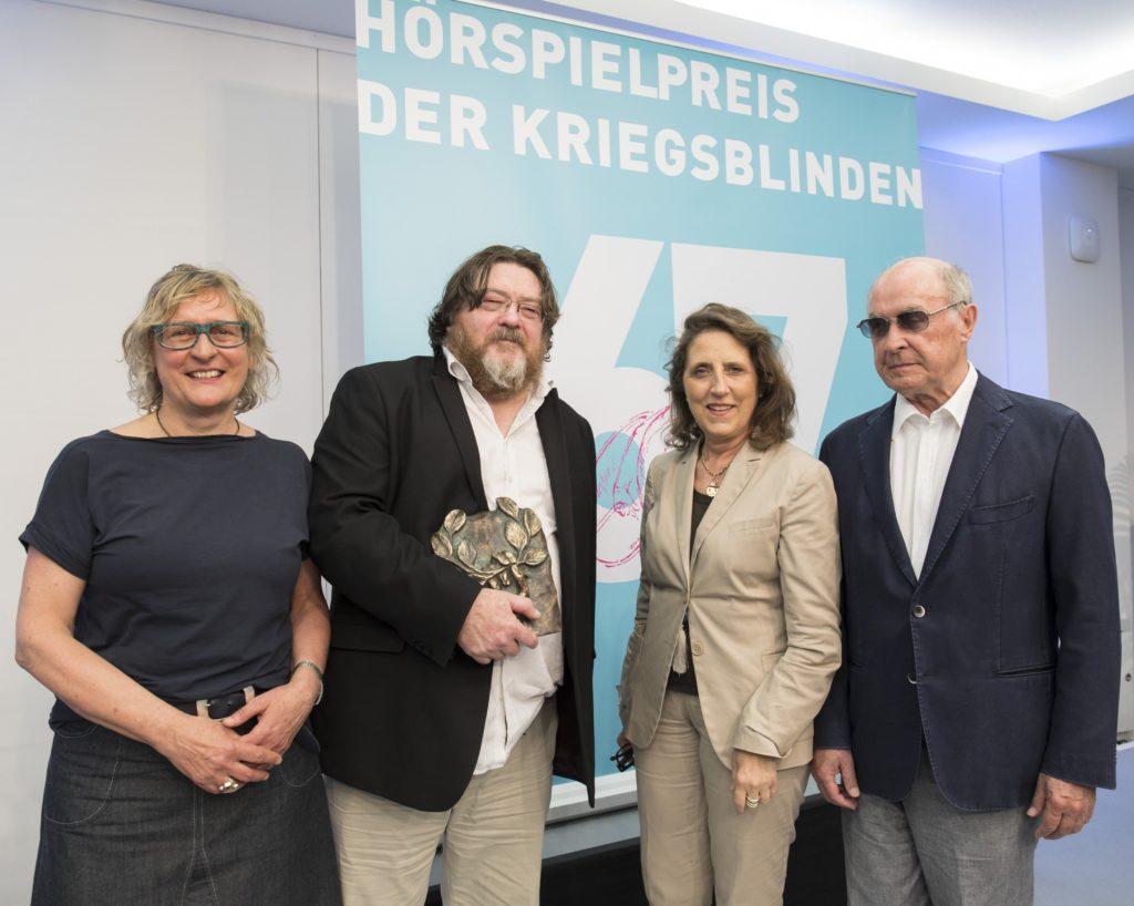 Jury-Vorsitzende Gaby Hartel, Preisträger John Burnside, Petra Müller (Geschäftsführerin Film- und Medienstiftung NRW), Hans-Dieter Hain (Bundesvorsitzender Bund der Kriegsblinden Deutschlands e.V.) © Film- und Medienstiftung NRW